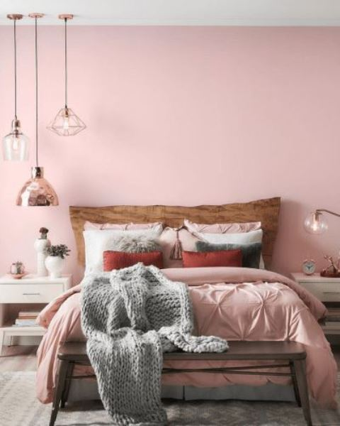 a chic and welcoming bedroom with light pink walls, light pink and white bedding for a soft and tender touch