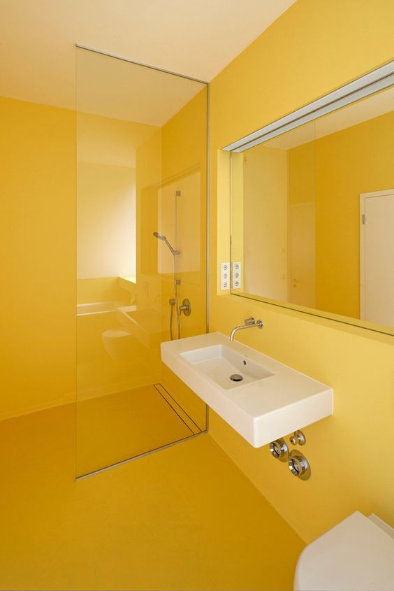 a minimalist sunny yellow bathroom done sleek and plain, with a statement mirror and a floating sink