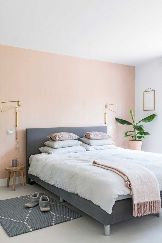 a boho chic bedroom with a light pink accent wall, an upholstered bed, pastel bedding and a printed rug