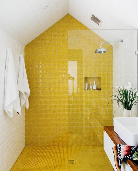 a modern bathroom with a lemon yellow tile shower and floor plus all white around looks bright and very fresh