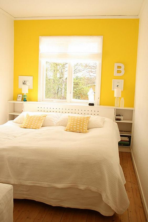 a small bedroom with a yellow accent wall and mustard pillows plus neutrals looks cool
