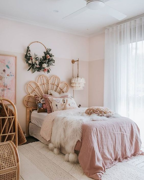 a boho chic bedroom with blush color block walls, pink bedding and rattan furniture is very glam