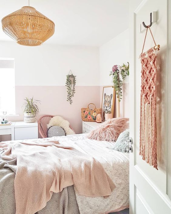 a boho chic space infused with light pink color block walls, pink bedding and a macrame hanging