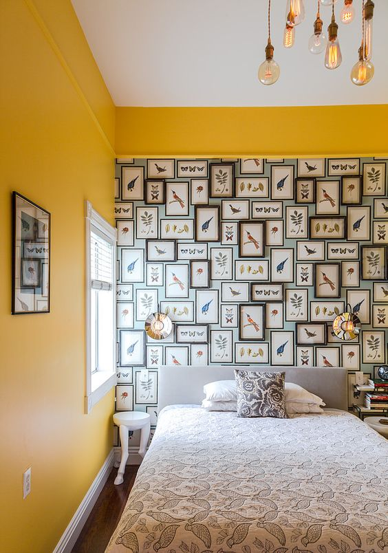 a bright bedroom with sunny yellow walls, a crazy bird gallery wall and printed bedding and pendant bulbs