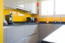 09 a minimalist kitchen with dove grey and grey minimal cabinets and a sunny yellow glass backsplash