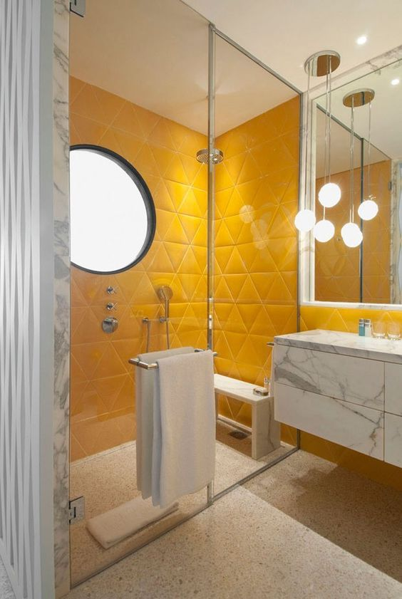 a bright contemporary bathroom with yellow triangle tile shower space, white marble and pendant lamps