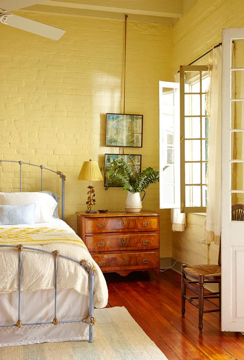 a bright country style bedroom with yellow brick walls, a yellow lamp and bedding
