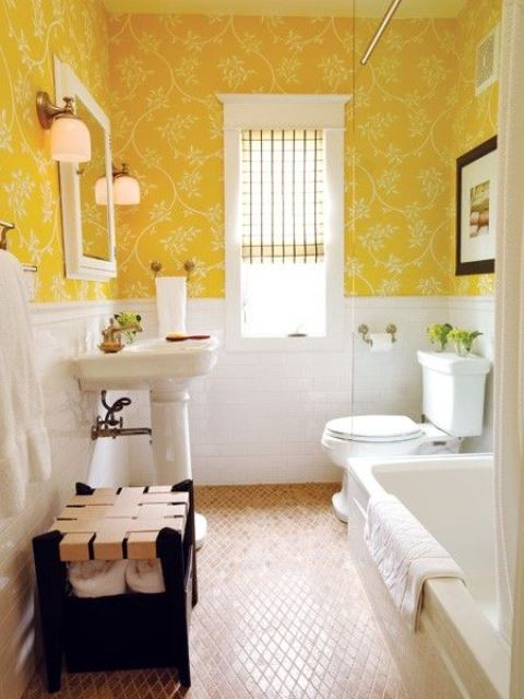 a bright vintage bathroom with sunny yellow wallpaper, white tiles and white appliances with a vintage feel