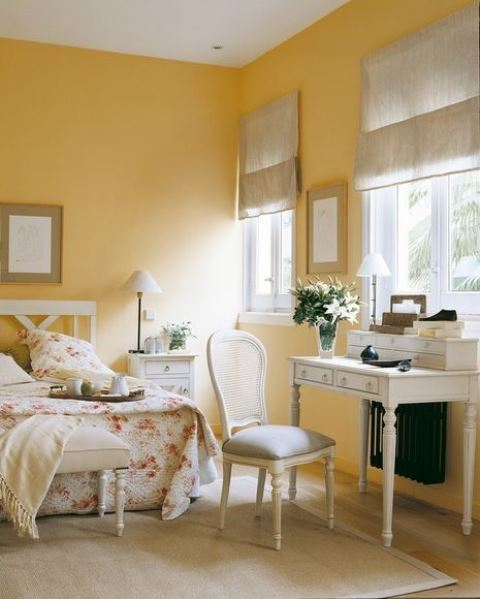 a charming vintage cottage bedroom with yellow walls, neutrals and floral prints is very romantic