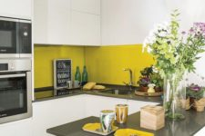 11 a small white and grey kitchen with plain cabinets and a sleek mustard tile backsplash for a touch of color