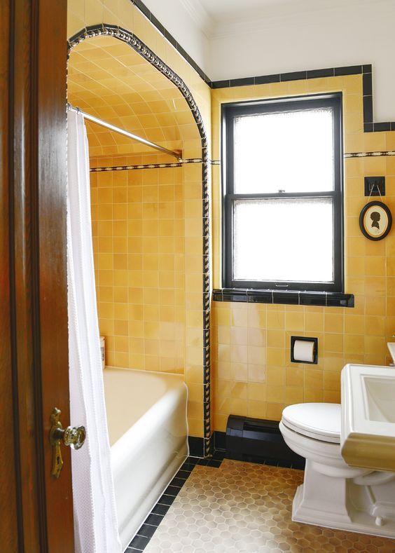 a bright vintage bathroom with yellow tiles, black touches for drama and white vintage appliances