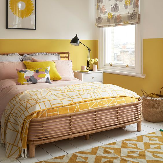 a cheerful bedroom with mustard color block walls, bright bedding, an artwork feels sunny and welcoming