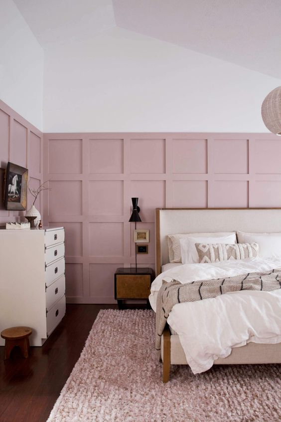 a gorgeous mid-century modern bedroom with pink panels on the walls and a soft pink rug to soften the monochromatic space