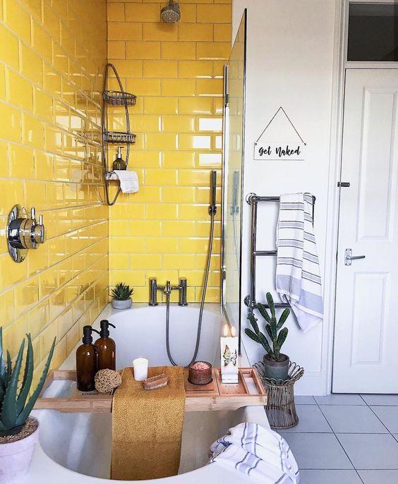 a catchy neutral bathroom with a grey tile floor and a sunny yellow tile backsplash around the bathtub
