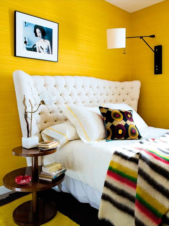 a cheerful whimsical bedroom with sunny yellow walls, a white upholstered bed and touches of black