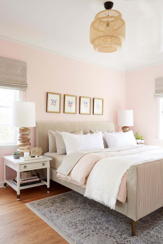a welcoming eclectic bedroom with light pink walls, neutral textiles and upholstery, a woven lamp and white nightstands