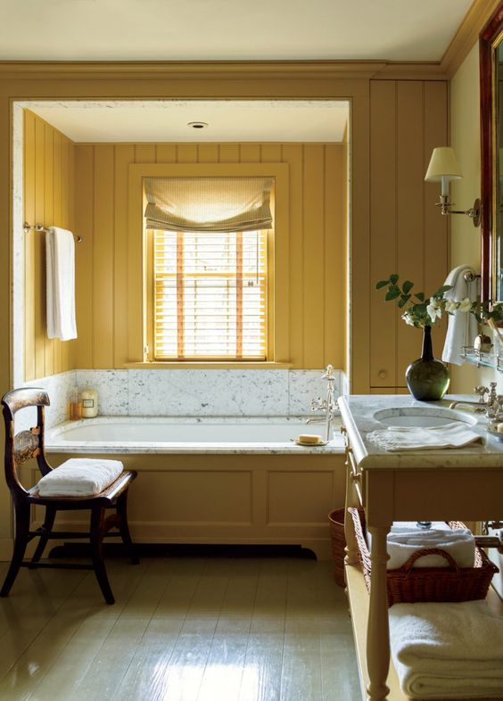a charming vintage bathroom with mustard beadboard walls, a vanity and a bathtub clad with mustard wood and neutrals
