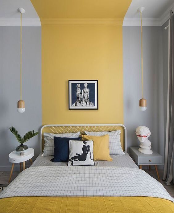 a stylish contemporary bedroom with a yellow stripe that goes up and mustard and grey bedding