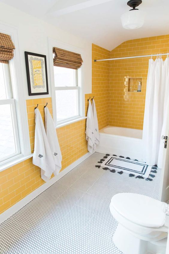 a cheerful bathroom with yellow tile walls, a penny tile floor and white appliances for a chic look