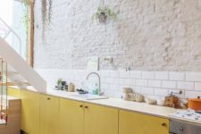 15 a contemporary kitchen with a brick wall and a white tile backsplash plus yellow plywood cabinets
