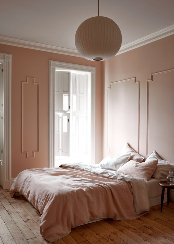 a warm minimalist bedroom with pink walls and pink and white bedding to make the space welcoming and chic