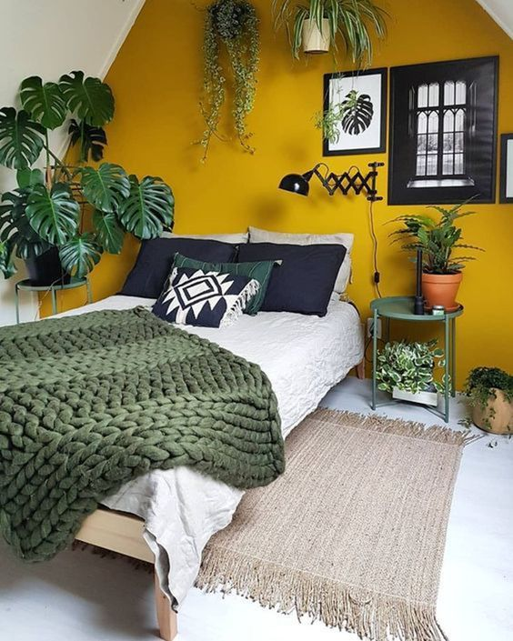 a cozy attic bedroom with a mustard accent wall and lots of potted greenery plus green, black and white bedding