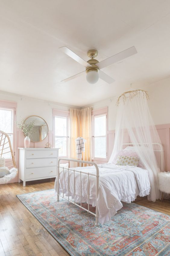 a romantic and airy girlish bedroom with pink panaled walls, a pink vase and window frames