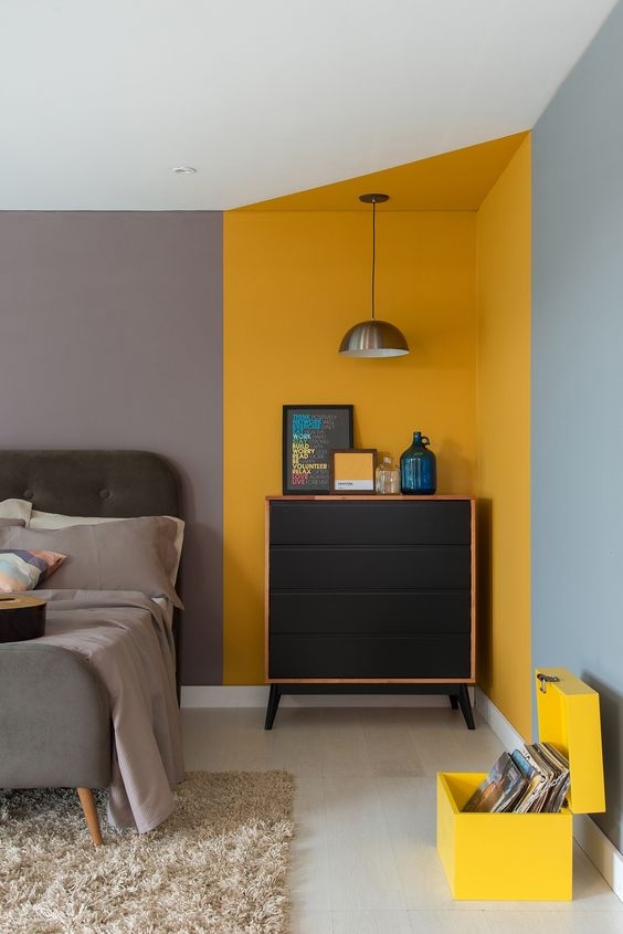 a contemporary bedroom with a yellow corner and a yellow chest for vinyl to spruce up the space with color