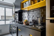17 a contrasting black kitchen with bright yellow touches – an open shelf and cutout handles is super bold