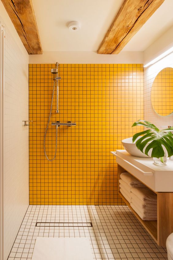a minimalist bathroom clad with white tiles, with wooden beams on the ceiling and a sunny yellow tile wall