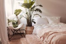 17 a simple boho bedroom with light pink walls, light pink bedding and a rug, a pallet bed and a comfy chair