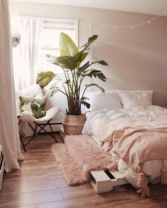 a simple boho bedroom with light pink walls, light pink bedding and a rug, a pallet bed and a comfy chair