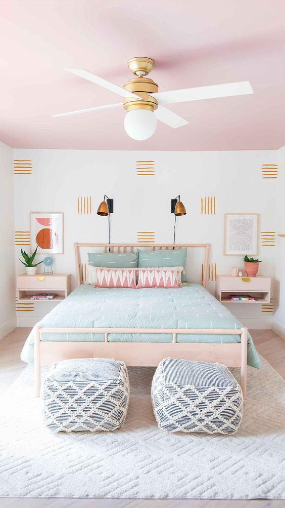a bright bedroom with a mid-century modern feel and a pink ceiling and pink pillows for a soft touch