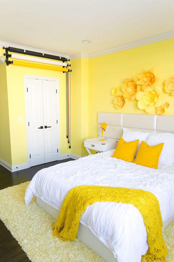 a colorful bedroom with lemon yellow walls, floral appliques on the wall and bright bedding