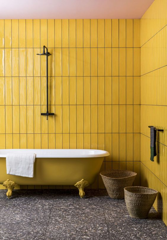 a minimal bathroom with mustard tile walls and a mustard bathtub, a dark stone tile floor and baskets