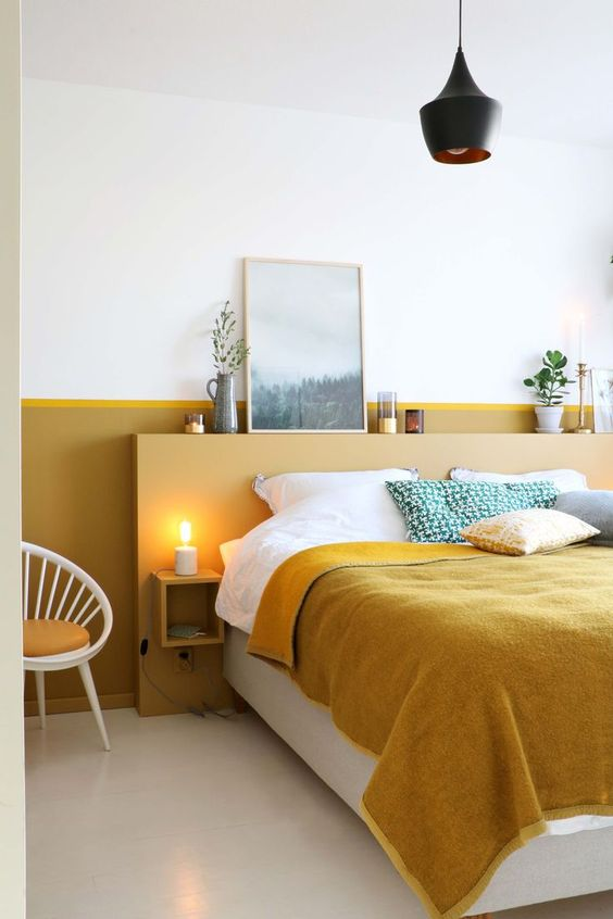 a chic and bold bedroom with a mustard color block wall and mustard and green bedding for a cozy feel