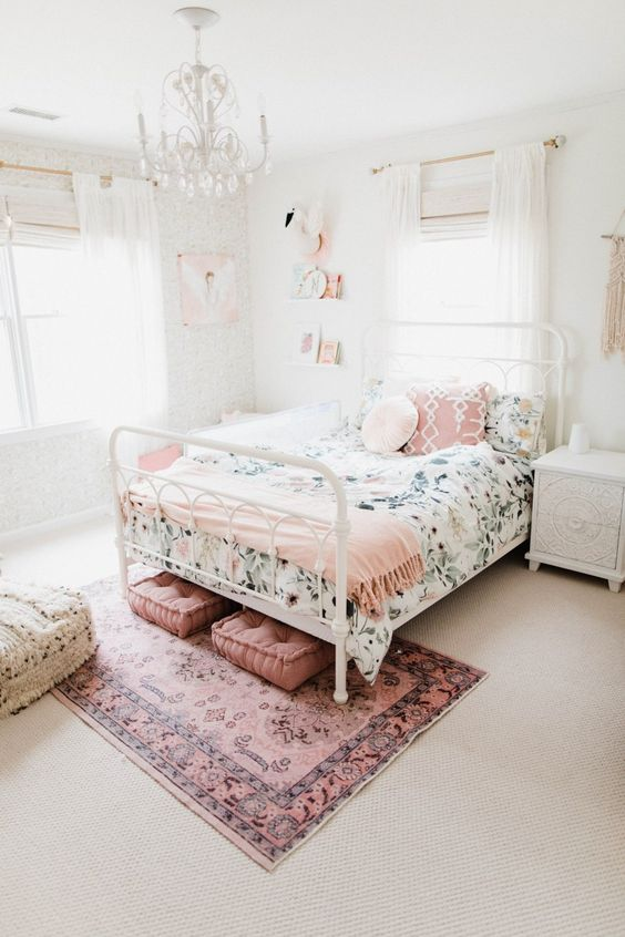 a chic bedroom in neutrals infused with pink - a pink rug, cushions, pillows, a blanket and some artworks and books