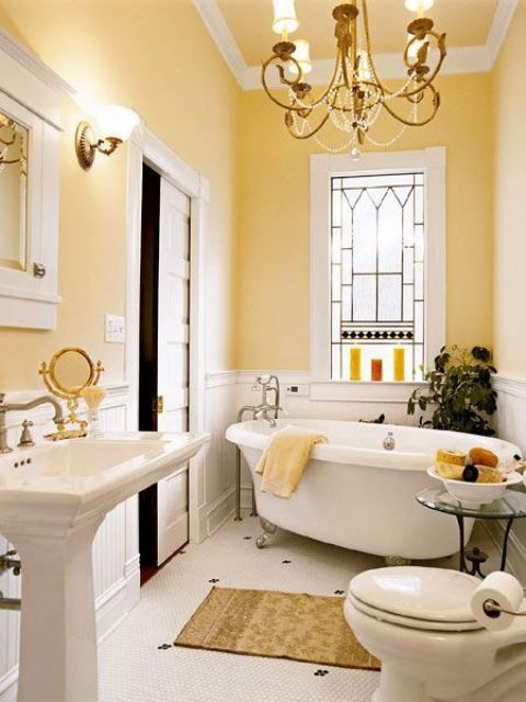 a beautiful pastel yellow bathroom with a crystal chandelier, vintage appliances and fixtures plus lamps
