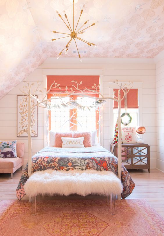 a fun bedroom with a light pink ceiling, a bright pink rug, a pink chair, pillow and coral Roman shades for a touch of color