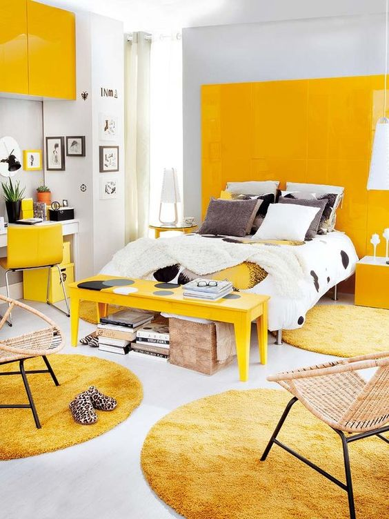 a bold modern bedroom with a yellow panel wall, a yellow bench, rugs, chair and a cabinet looks extra bright
