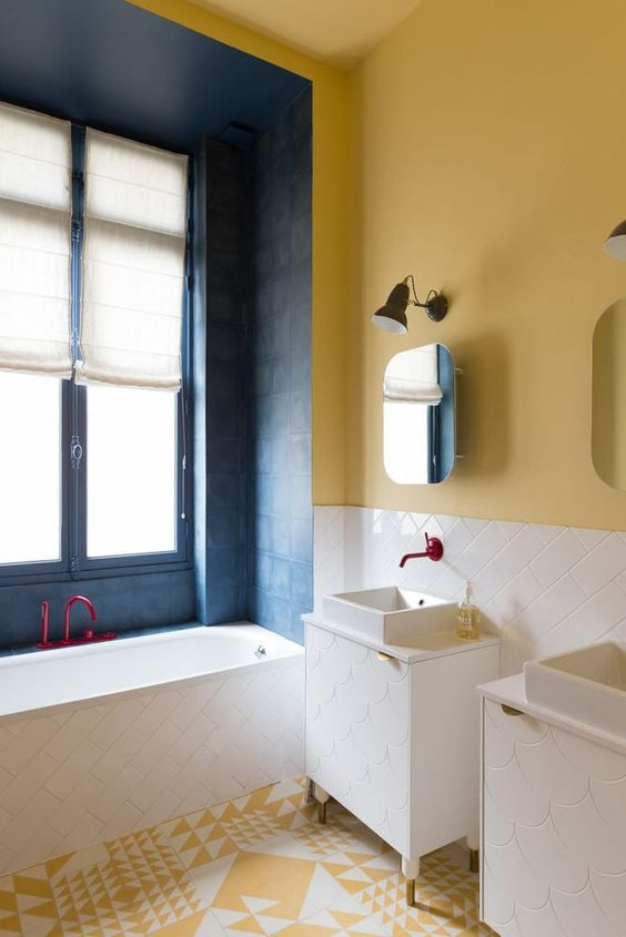 a bright bathroom with a yellow wall and a yellow and white tile floor, a blue bathtub zone and white tiles