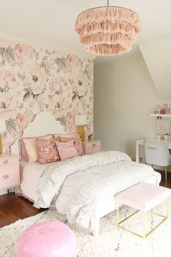 a girlish bedroom with a floral wallpaper wall, pink nightstands and ottomans, a pink tassel chandelier and printed pillows