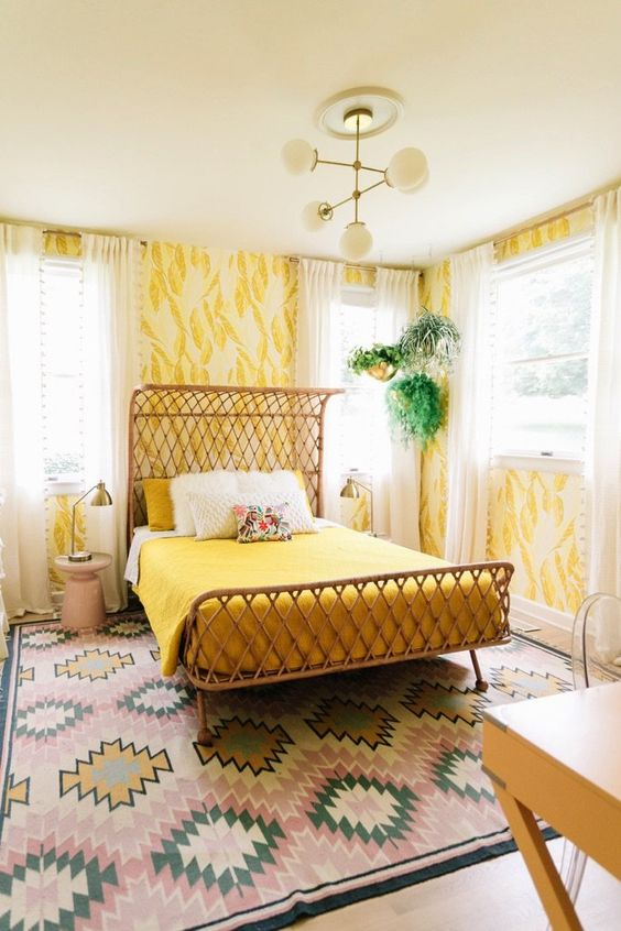 a bright mid century modern bedroom with yellow wallpaper walls, bright mustard bedding and a bright rug