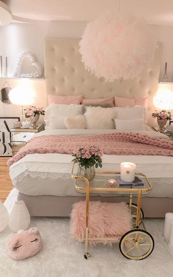 a glam bedroom with pink pillows, a blanket, some cushions and touches of shiny gold