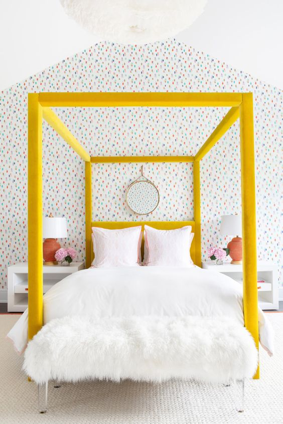 a bright modern girlish bedroom with a yellow velvet upholstered bed that is a centerpiece here