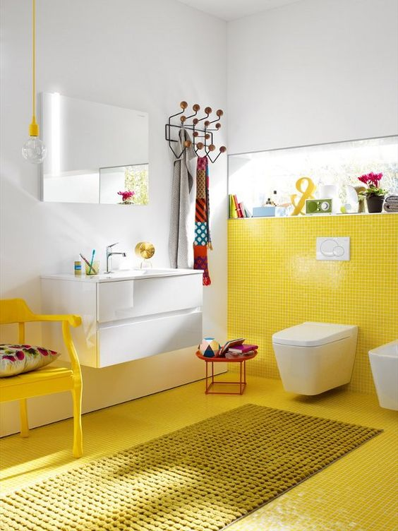 a colorful bathroom with a yellow tile wall and floor plus a chair and all white around looks quirky and cool