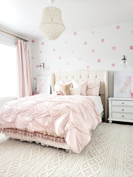 a lovely bedroom with light pink curtains and a draped bedspread and pillows plus a pink polka dot wallpaper wall