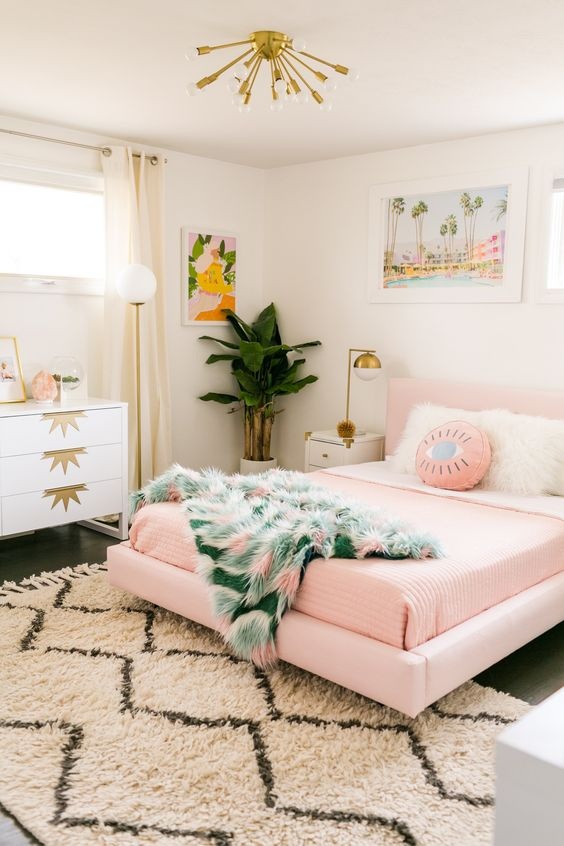 a mid-century modern bedroom with a glam feel shows off a pink floating bed and pink bedding for a soft touch
