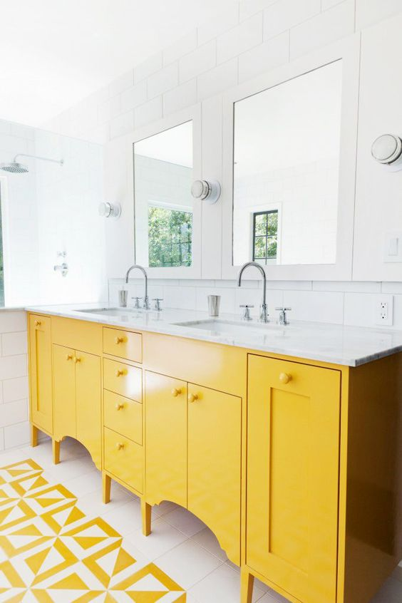 a serene white bathroom with white subway tiles and a yellow vanity plus yellow and white mosaic tiles
