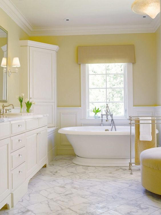 a vintage lemon-infused bathroom with light yellow walls, lemon furniture and textiles and all white around looks warming
